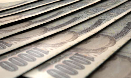 staggered: A macro close-up view showing the detail of japanese yen banknotes laid out and overlapping in a staggered row