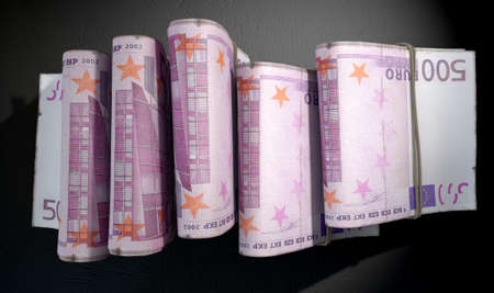 doubled: A close-up view of five wads of folded over stacks of euro banknotes each bound infomally by a rubber band set out in a domino formation on an isolated dark studio background Stock Photo