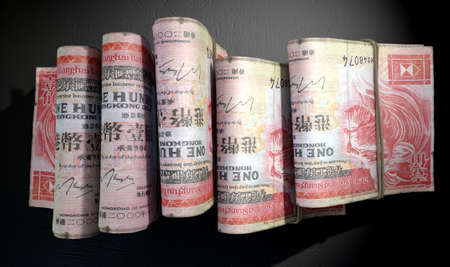wads: A close-up view of five wads of folded over stacks of hong kong dollar banknotes each bound infomally by a rubber band set out in a domino formation on an isolated dark studio background Stock Photo