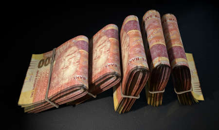 rand: A close-up view of five wads of folded over stacks of south african rand banknotes each bound infomally by a rubber band set out in a domino formation on an isolated dark studio background