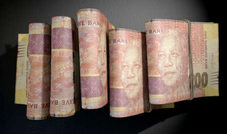 doubled: A close-up view of five wads of folded over stacks of south african rand banknotes each bound infomally by a rubber band set out in a domino formation on an isolated dark studio background