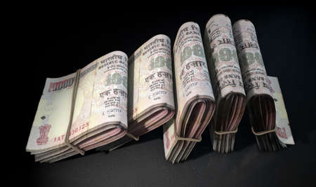 five rupee: A close-up view of five wads of folded over stacks of indian rupee banknotes each bound infomally by a rubber band set out in a domino formation on an isolated dark studio background