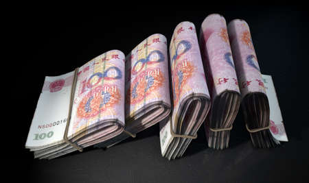 doubled: A close-up view of five wads of folded over stacks of chinese yuan banknotes each bound infomally by a rubber band set out in a domino formation on an isolated dark studio background