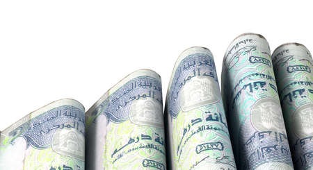 doubled: A close-up view of five wads of folded over stacks of dirham banknotes each bound infomally by a rubber band set out in a domino formation on an isolated white studio background