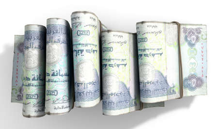 illicit: A close-up view of five wads of folded over stacks of dirham banknotes each bound infomally by a rubber band set out in a domino formation on an isolated white studio background