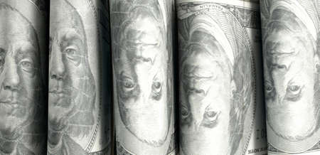 doubled: A close-up view of five wads of folded over stacks of us dollar banknotes each bound infomally by a rubber band set out in a domino formation on an isolated white studio background
