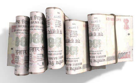 doubled: A close-up view of five wads of folded over stacks of indian rupee banknotes each bound infomally by a rubber band set out in a domino formation on an isolated white studio background