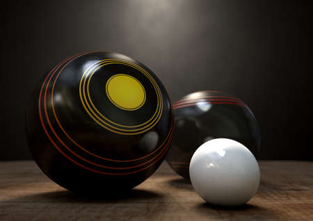 Two wooden lawn bowling balls surrounding a white jack on a wooden isolated dark studio background
