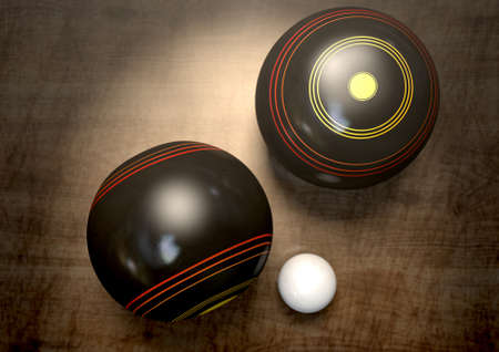 bowl game: Two wooden lawn bowling balls surrounding a white jack on a wooden isolated dark studio background