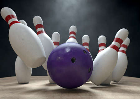 An arrangement of white and red used vintage bowling pins being struck by a bowling ball on a wooden bowling alley surface on a dark background Banque d'images