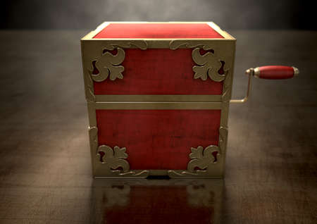 embellished: An ornate antique closed jack-in-the-box mad of red wood and gold trimmings on a dark studio background under a spotlight
