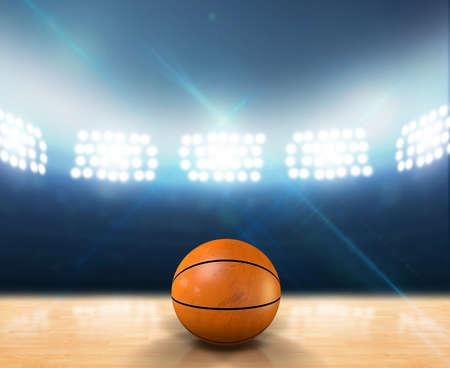 cancha de basquetbol: Una cancha de baloncesto cubierta con una bola naranja en un piso de madera sin marca bajo los focos de iluminaci�n