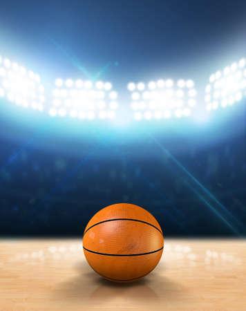 An indoor basketball court with an orange ball on an unmarked wooden floor under illuminated floodlights Stock Photo