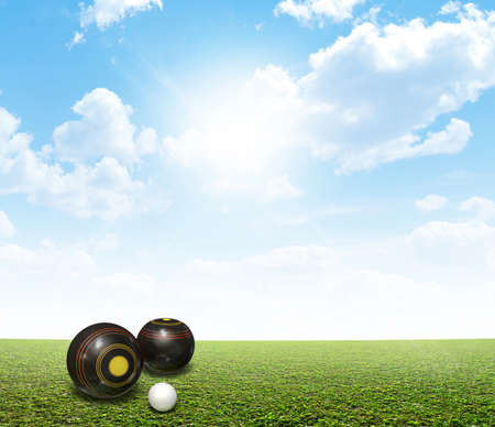 bowl game: A set of wooden lawn bowls next to a jack on a perfect flat green lawn against a blue sky with white clouds