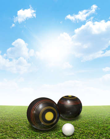 A set of wooden lawn bowls next to a jack on a perfect flat green lawn against a blue sky with white clouds