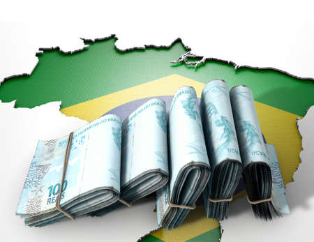 The shape of the country of Brazil in the colours of its national flag recessed into an isolated white surface with a wad of folded Brazilian real notes resting on it photo