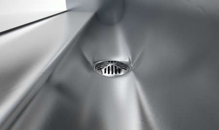 latrine: A a closeup of the drain of a stainless steel trough style urinal on an isolated white studio background