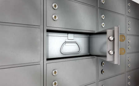 safety box: A closeup of a wall of closed metal safety deposit boxes with one open revealing its contents inside