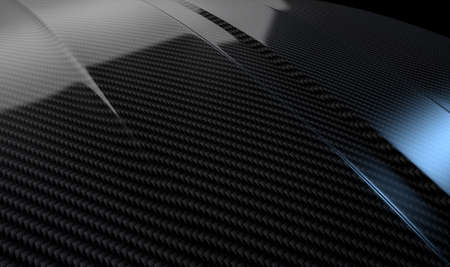 An abstract section of the contours of a carbon fibre automobile bonnet with dramatic lighting on a dark studio background Standard-Bild