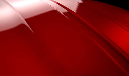 An abstract section of the contours of a cherry red automobile bonnet with dramatic lighting on a dark studio background