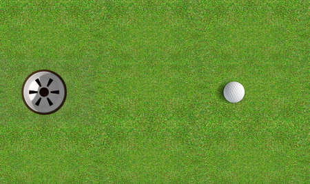 A view of a perfectly manicured golf putting green and hole with a ball on the edge in the daytime Stock Photo