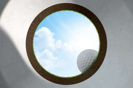 holed: A worms eye view out of a golf putting green hole with a ball on the edge in the daytime