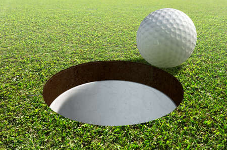 holed: A view of a perfectly manicured golf putting green and hole with a ball on the edge in the daytime Stock Photo