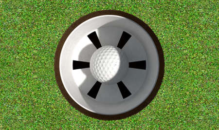 holed: A view of a perfectly manicured golf putting green and hole with a ball inside in the daytime