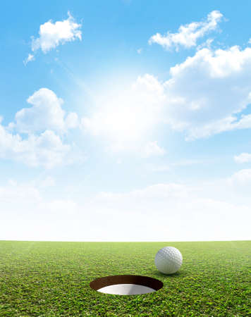 holed: A view of a perfectly manicured golf putting green and hole with a ball on the edge in the daytime on a blue sky background