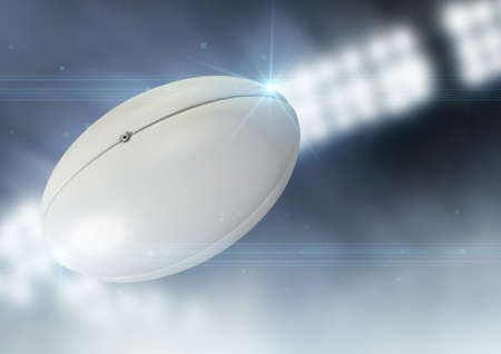 rugby field: A regular rugby ball flying through the air on an indoor stadium background during the night Stock Photo