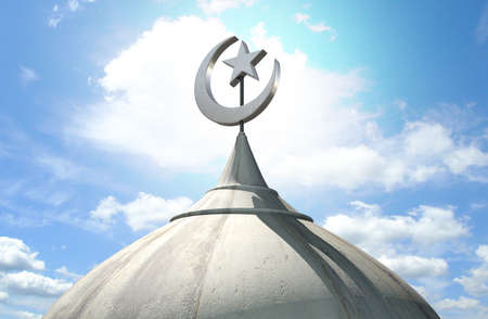 A closeup of the top of a mosque minaret with a cupola dome and an islamic crescent moon and star on a blue sky background