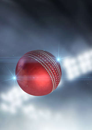 floodlit: A regular red cricket ball flying through the air on an indoor stadium background during the night