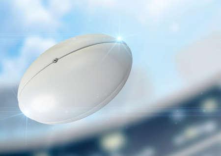 pelota de rugby: Una pelota de rugby regulares volando por el aire sobre un fondo estadio durante el día Foto de archivo