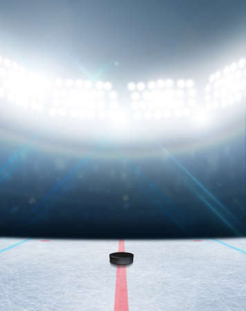 hockey games: A generic ice hockey ice rink stadium with a frozen surface and a hockey puck under illuminated floodlights
