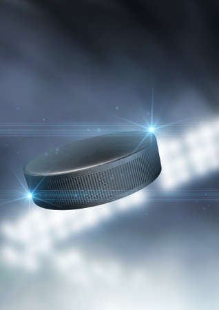 A regular ice hockey puck flying through the air on an indoor stadium background during the night
