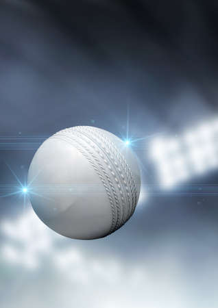 cricket game: A regular white cricket ball flying through the air on an indoor stadium background during the night Stock Photo