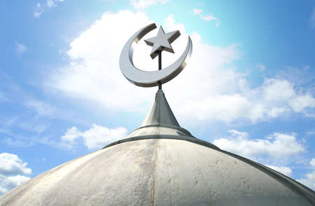 islamic: A closeup of the top of a mosque minaret with a cupola dome and an islamic crescent moon and star on a blue sky background