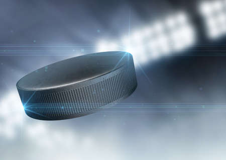 hockey puck: A regular ice hockey puck flying through the air on an indoor stadium background during the night