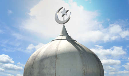 cupola: A closeup of the top of a mosque minaret with a cupola dome and an islamic crescent moon and star on a blue sky background
