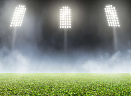 unmarked: A generic outdoor stadium with an unmarked green grass pitch with an eerie mist at night under illuminated floodlights