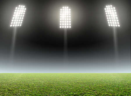 unmarked: A generic outdoor stadium with an unmarked green grass pitch at night under illuminated floodlights Stock Photo