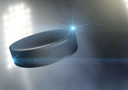hockey hielo: Un disco de hockey sobre hielo regular de volar por el aire en un fondo estadio al aire libre durante la noche