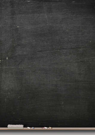 A rectangular black chalkboard with a metal frame with a wooden ledge chalk and a duster