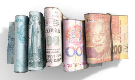 staggered: Five wads of folded stacks of banknotes representing the BRICS countries each bound infomally by a rubber band set out in a domino formation on an isolated white studio background