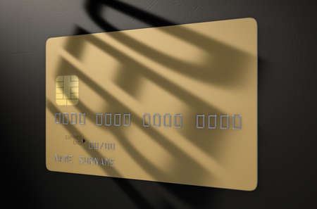 owing: A closeup view of a gold generic blank bank credit card with a shadow casting the word debt over it on an isolated dark studio background Stock Photo