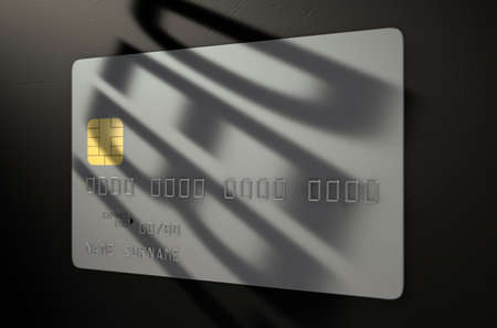 owing: A closeup view of a silver generic blank bank credit card with a shadow casting the word debt over it on an isolated dark studio background
