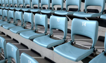 A section of numbered stadium seating with blue chairs set in rows on a sloping concrete bank