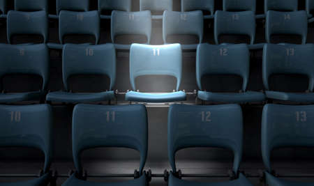 focal point: A section of numbered stadium seating set in rows oin the dark with one seat  being singled out by a spotlight