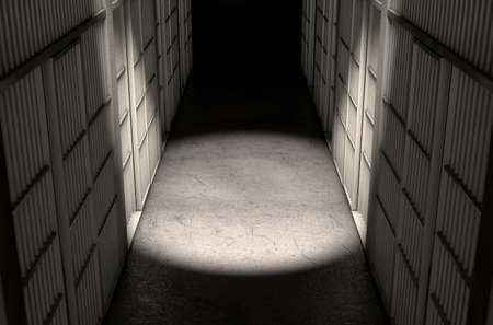correctional facility: A direct top view of a row of closed jail cells between a concrete aisle lit by a single dramatic spotlight
