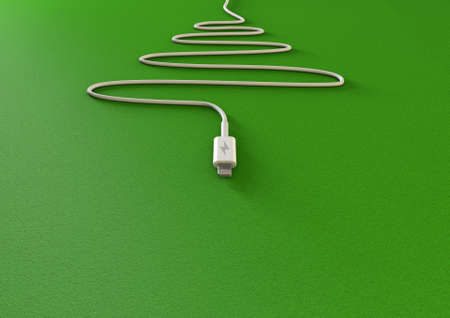fiestas electronicas: A mobile phone charger draped in the shape of a christmas tree on an isolated green background with copy space